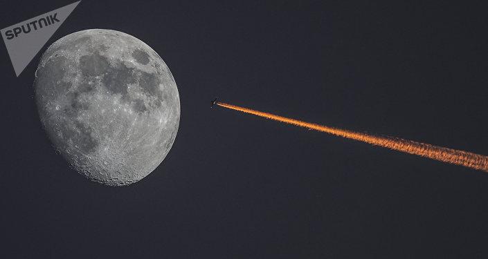 Самолет в небе на фоне растущей луны. Архивное фото