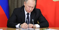 Президент РФ Владимир Путин во время подписания документа. Архивное фото