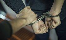 Мужчина держит арестованного за руки. Иллюстративное фото