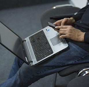 Мужчина с ноутбуком и мобильным телефоном. Архивное фото