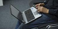 Мужчина с ноутбуком и мобильным телефоном в Бишкеке. Архивное фото