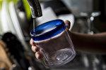 Девушка набирает воду в стакан из-под крана. Архивное фото