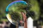 Мальчик лопает мыльный пузырь. Архивное фото