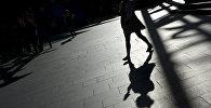 Тень девушки идущей по городу. Архивное фото