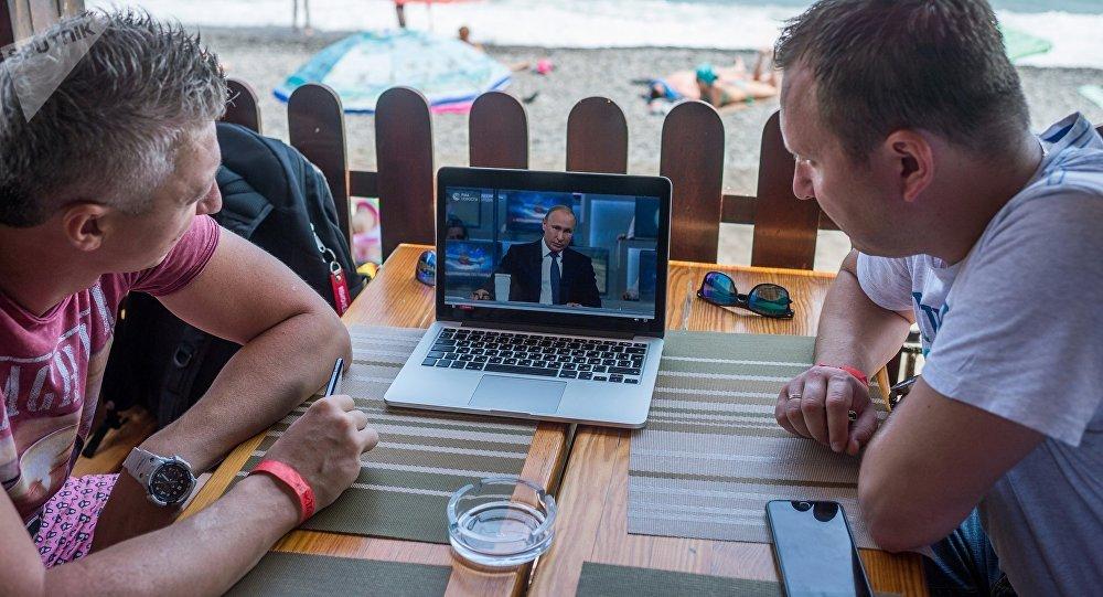 Мужчины смотрят трансляцию прямой линии с президентом России Владимиром Путиным.