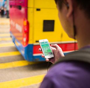 Парень с телефоном идет по улице. Архивное фото