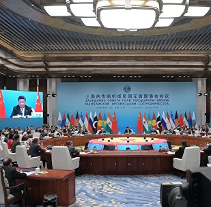 Президент РФ Владимир Путин и председатель КНР Си Цзиньпин (на экране) принимают участие в заседании Совета глав государств - членов Шанхайской организации сотрудничества (ШОС) в расширенном составе в Циндао.