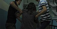 Девушку насильно уносят из подъезда. Иллюстративное фото