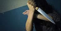Девушка с кухонным ножом в руке. Иллюстративное фото