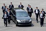 Сотрудники службы безопасности лидера КНДР Ким Чен Ына сопровождают его автомобиль перед встречей с президентом Южной Кореи в Панмундже, Южная Корея, 27 апреля 2018 года