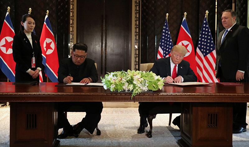 Президент США Дональд Трамп и лидер КНДР Ким Чен Ын во время подписания документа по итогам встречи в Сингапуре. 12 июня 2018 года