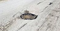 Оштун Ноокатында унаа жолдун аң-чөнөктөрүнө толгон сууну тазалабай туруп, анын үстүнө асфальт төшөп жатышат