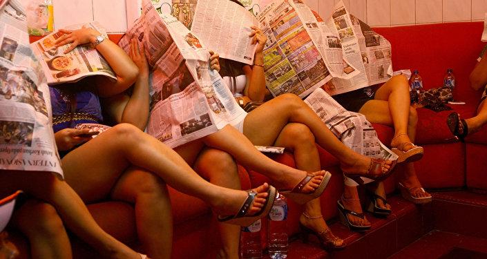Работницы секс-притона закрывают лица газетами. Архивное фото
