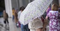 Женщина с зонтом на одной из улиц Бишкека во время дождя