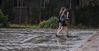 Девушки во время дождя на одной из улиц Бишкека. Архивное фото