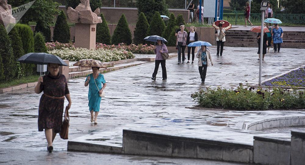 Горожане с зонтами на аллее молодежи в Бишкеке во время дождя