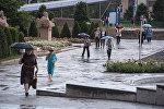 Горожане с зонтами на аллее молодежи в Бишкеке во время дождя. Архивное фото