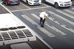 Пенсионер с трудом переходил дорогу, полицейский перенес его на себе. Видео