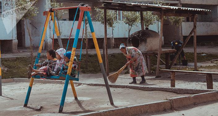 Женщина убирается во дворе жилого квартала поселка Восточный города Сулюкта. Архивное фото