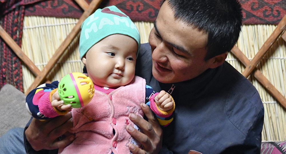 Мужчина нянчит своего ребенка. Архивное фото