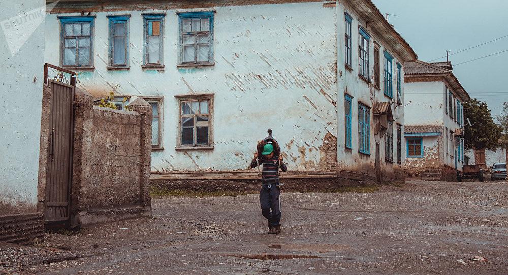 Сельский мальчик несет седло среди двухэтажных деревянных жилых домов из сруба в поселке 18-й Шурф города Сулюкта Баткенской области. Архивное фото