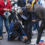 Пожилому мужчине помогают зашнуровать обувь после окончания Айт-намаза