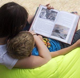 Женщина и ребенок читают книгу. Архивное фото