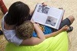Женщина читает книгу ребенку. Архивное фото