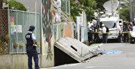 Сотрудник полиции на месте, где девушка была убита упавшей стеной вызванной землетрясением в префектуре Осака на западе Японии. 18 июня 2018 года