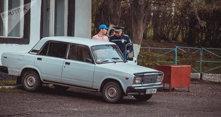Сотрудник ГАИ (ГУОБДД МВД) проверяет документы у водителя. Архивное фото
