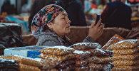Торгующая сухофруктами женщина на центральном рынке города Исфана смотрит в мобильный телефон . Архивное фото