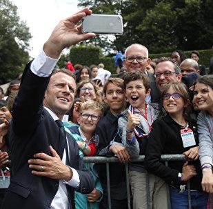 Президент Франции Эммануэль Макрон делает селфи с детьми во время церемонии, посвященной 78-й годовщине призыва сопротивления последнего генерала Шарля де Голля на мемориале Мон-Валериуса в Сюрене, недалеко от Парижа. Франция, 18 июня 2018 года