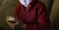 Мальчик с телефоном в руке. Архивное фото