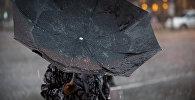 Женщина с зонтом во время сильного дождя с ветром. Архивное фото