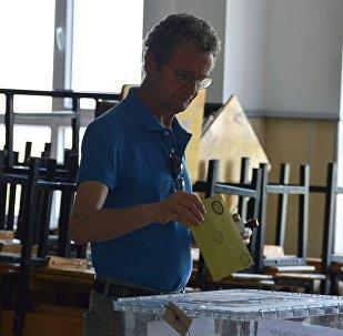 Мужчина опускает бюллетень в урну на одном из избирательных участков в Анкаре.