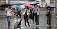 Прохожие идут по улице во время сильного дождя. Архивное фото