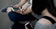 Девушка и парень с телефонами в руке. Архивное фото