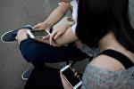 Девушка и парень с телефонами в руках. Архивное фото