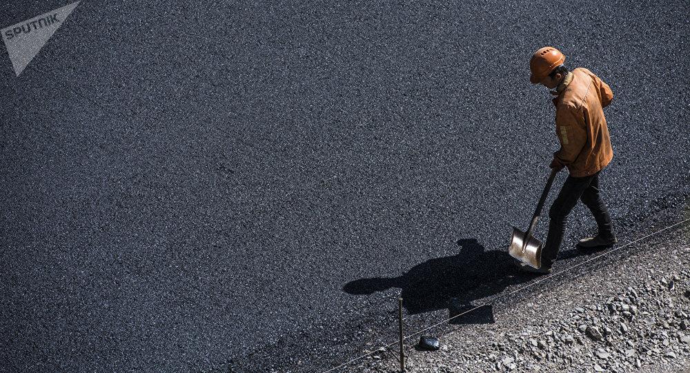 Дорожник во время укладки асфальта. Архивное фото
