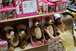 Девочка у полки с игрушками - персонажами российского мультфильма Маша и медведь в детском магазине. Архивное фото