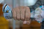 Мужчина сжимает казахский тенге в кулаке. Архивное фото