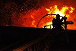Сотрудник пожарной службы во время тушения пожара. Архивное фото