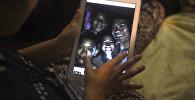 Члены семьи смотрят на фотографии пропавших мальчиков, которые сделали спасатели-дайверы в пещере, когда все члены детской футбольной команды и их тренер были найдены живыми. 2 июля 2018