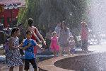 Дети едят мороженое в жару у фонтана напротив ЦУМа в Бишкеке. Архивное фото
