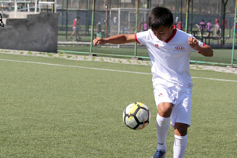 Подросток из Кыргызстана Ырыскельди Тыныбеков вынесет мяч на четвертьфинальной игре Чемпионата мира по футболу между сборными России и Хорватии