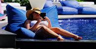 Девушка отдыхает у бассейна. Архивное фото