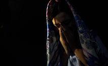 Девушка в платке плачет в темной комнате. Иллюстративное фото