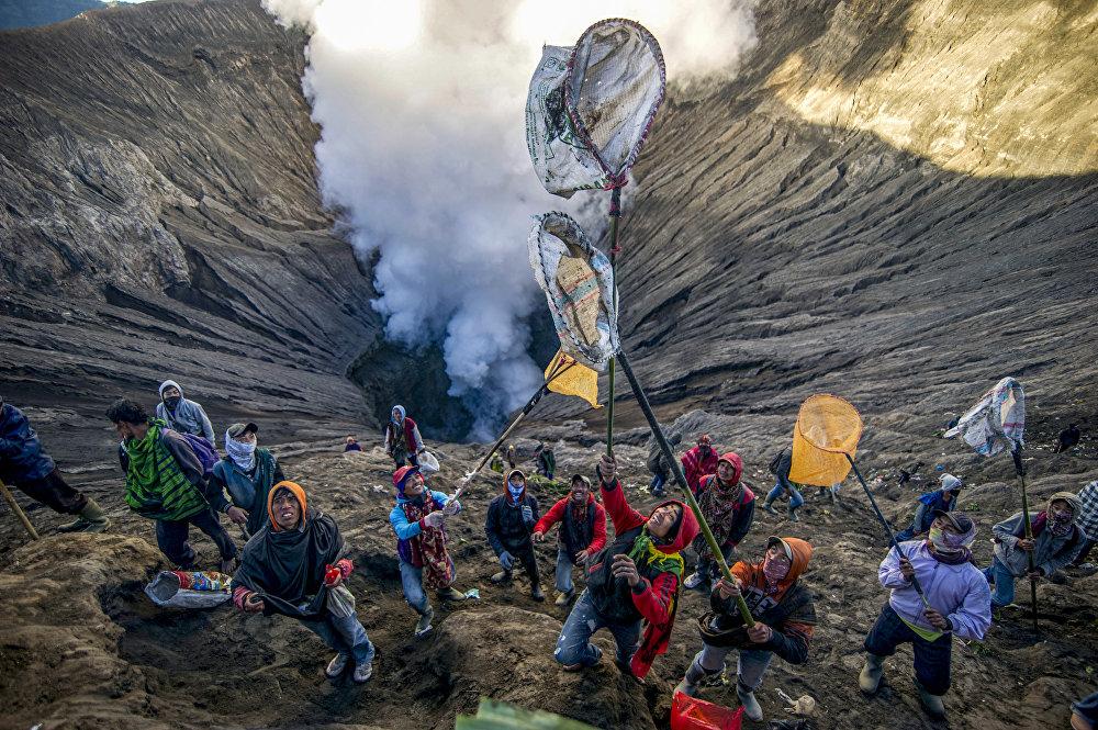 Индонезиядагы фестиваль учурунда адамдар Бромо жанар тоосунун кратерине ыргытылып жаткан тартууларды тосуп алууга аракеттенип жатышат