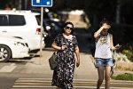 Женщина и девушка идут по одной из улиц Бишкека в аномально жаркий день. Архивное фото