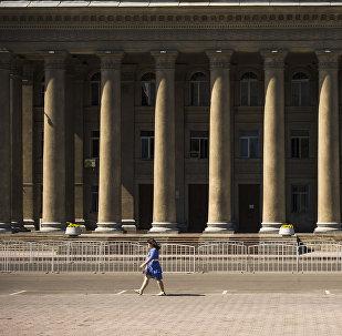 Девушка идет у здания правительства в Бишкеке. Архивное фото